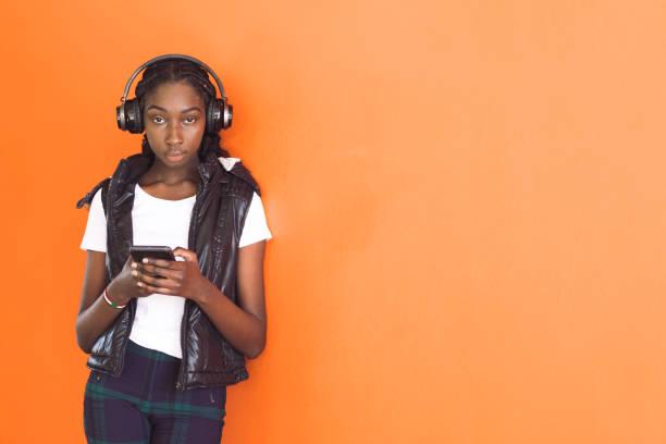 African Australian Teenage Girl Listening To Music Under Headphones stock photo