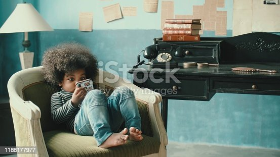 Little cute african-american afro girl(2-3 years) watching video from smart phone, Surfing the net, 4K Resolution, Handheld Shot