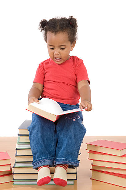 African baby reading sitting on a pile of books stock photo