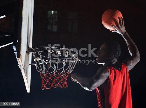 istock African basketball player playing on court at night 900119888