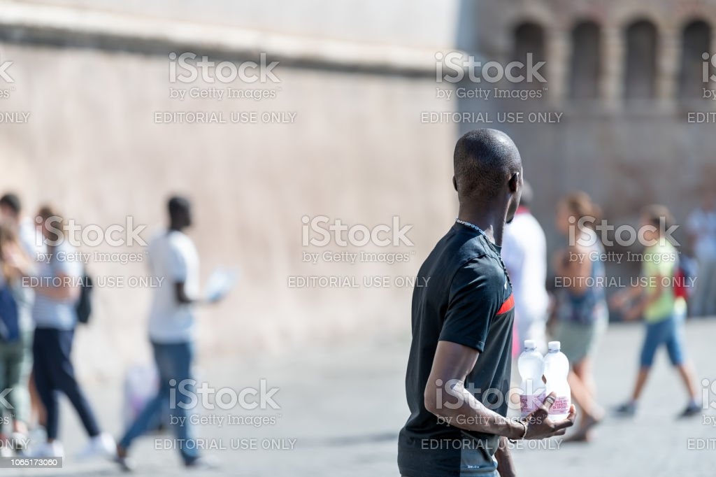 African black male, man, immigrant, street vendor, seller selling bottled bottles of water, walking road sidewalk with Italian people, crowd in Roma stock photo