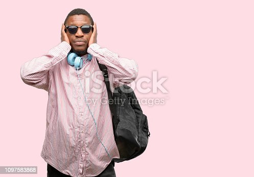 African black man student covering ears ignoring annoying loud noise, plugs ears to avoid hearing sound. Noisy music is a problem.