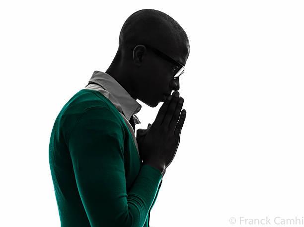 african black man thinking pensive praying silhouette one african  black man  thinking pensive praying silhouette  in silhouette studio on white background back lit stock pictures, royalty-free photos & images