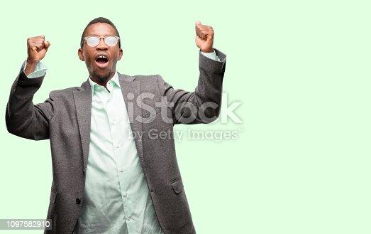 925466128istockphoto African black man wearing jacket happy and excited celebrating victory expressing big success, power, energy and positive emotions. Celebrates new job joyful 1097582910