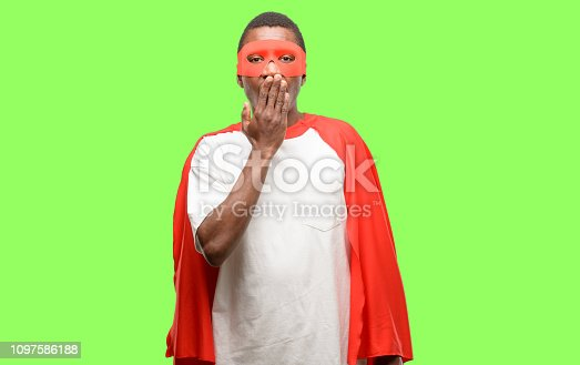 African black super hero man covers mouth in shock, looks shy, expressing silence and mistake concepts, scared