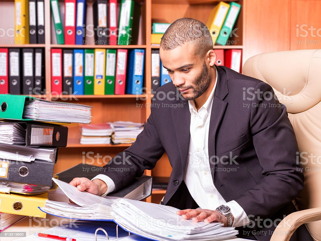 african bookkeeper working with papers in the office stock photo