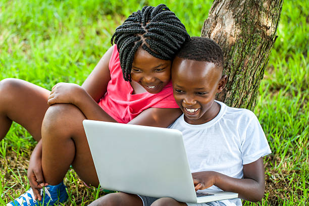 African boy and girl playing on laptop. stock photo