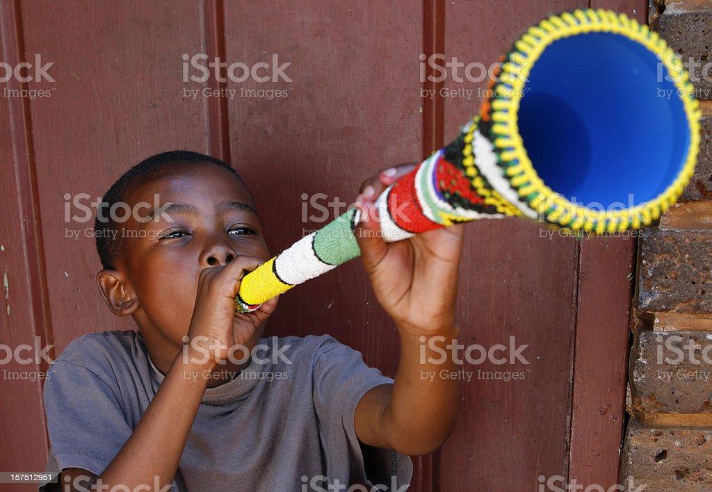 African boy blowing a Vuvuzela stock photo