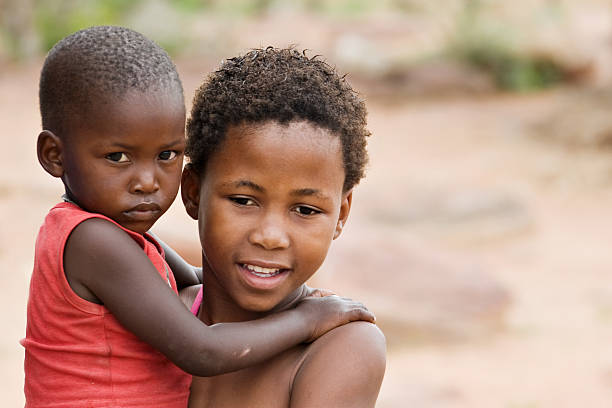 African boy carrying his brother stock photo