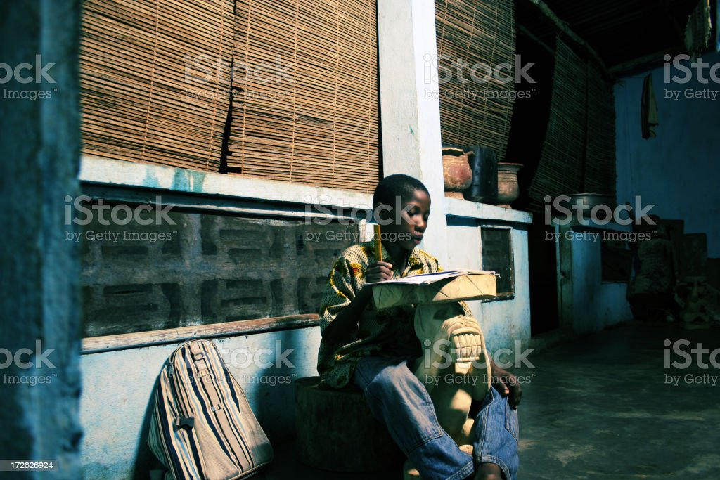 african boy doing homework stock photo