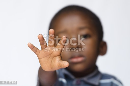 istock African boy holding his hand out as a STOP sign for racism and abuse 842147906