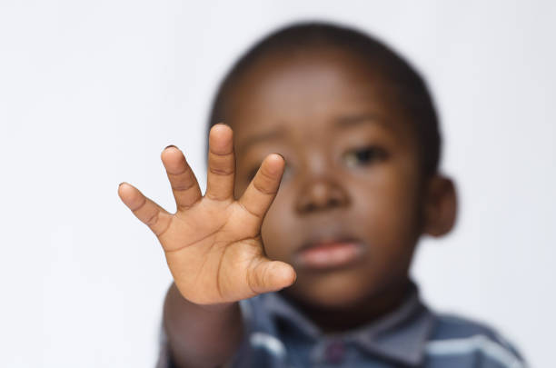 African boy holding his hand out as a STOP sign for racism and abuse stock photo