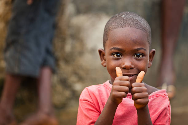 African Boy A young African boy sitting near a public water pump smiling white giving a thumbs up. developing countries stock pictures, royalty-free photos & images