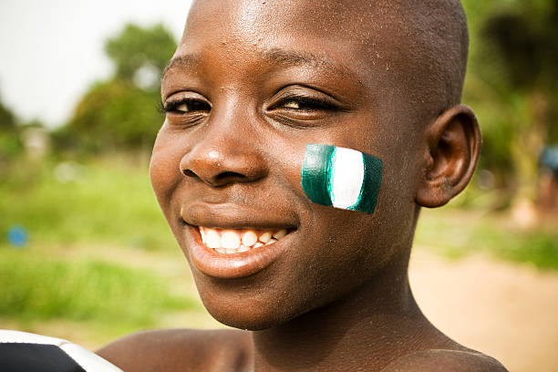 African boy with flag of Nigeria on a cheek stock photo