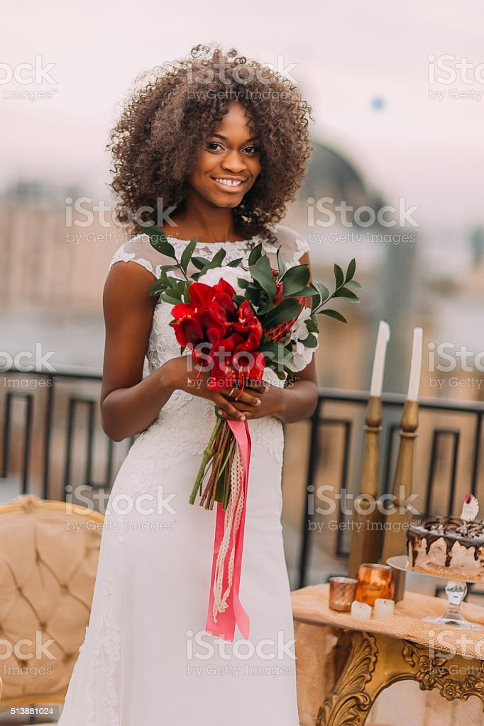 African bride cheerfully smiling with bouquet of red flowers in stock photo