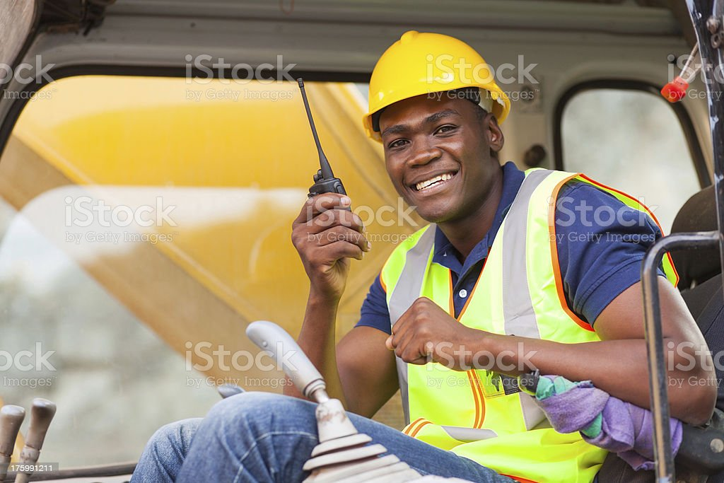 african bulldozer operator talking on walkie talkie royalty-free stock photo