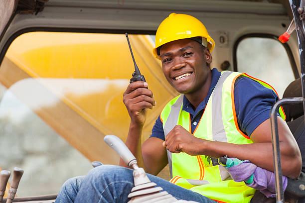 african bulldozer operator talking on walkie talkie stock photo