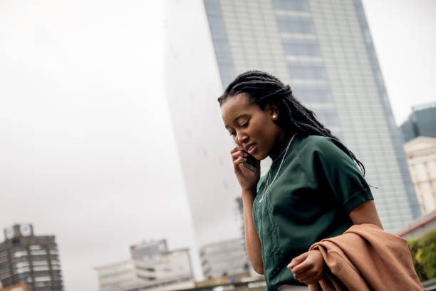 African Business woman using her mobile phone on her commute to work stock photo