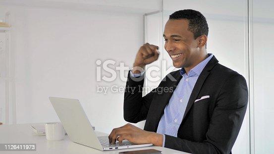 888751614 istock photo African Businessman Celebrating Success, Working on Laptop 1126411973