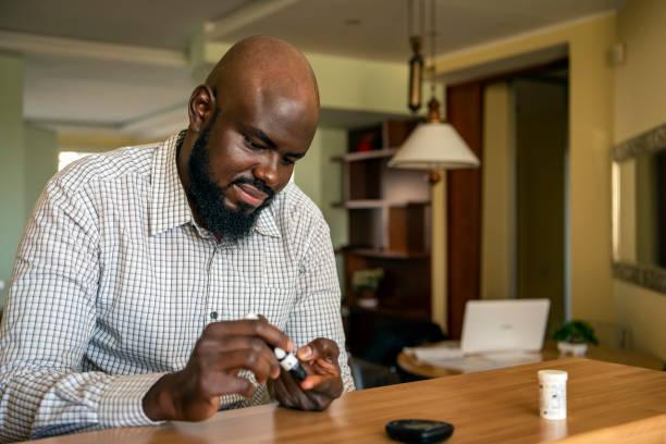 afrikaanse zakenman doen bloedsuiker test thuis - bloedsuikertest stockfoto's en -beelden