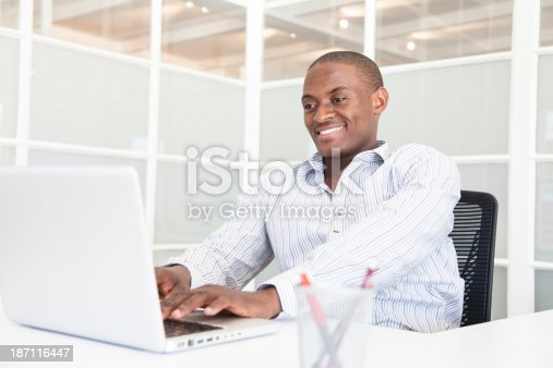 1053499704 istock photo African businessman doing research at work with a smile. 187116447