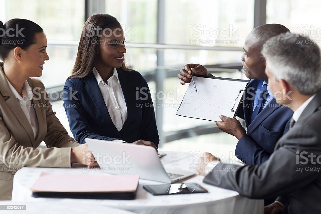 african businessman explaining sales graph to colleagues stock photo