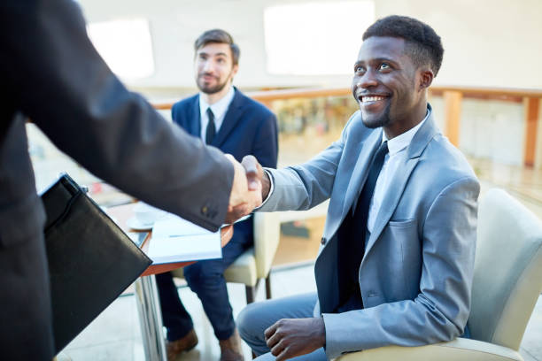 African Businessman Greeting New Partner Portrait of smiling young African-American  businessman shaking hands with partner, sitting at table in meeting foreign affairs stock pictures, royalty-free photos & images