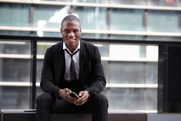 african businessman holding mobile phone stock photo