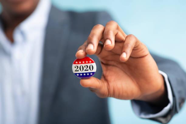 afrikalı işadamı cumhurbaşkanlığı seçimleri için oy düğmesini tutarak 2020 - başkanlık seçimleri stok fotoğraflar ve resimler