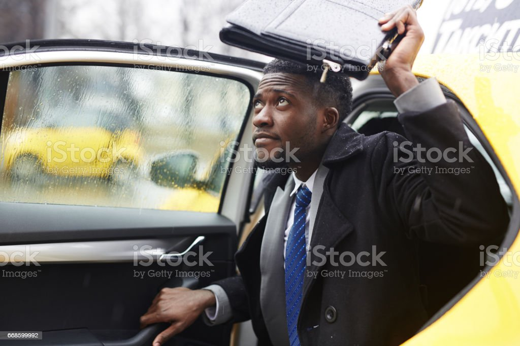 African Businessman Leaving Taxi in Rain stock photo