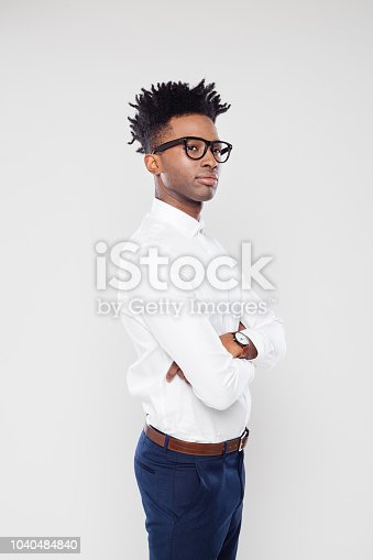 Portrait of african businessman standing with and attitude on white background. African man in formal wear wearing eyeglasses looking away with his arms crossed.