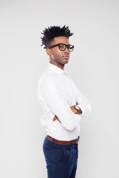 African businessman looking away Portrait of african businessman standing with and attitude on white background. African man in formal wear wearing eyeglasses looking away with his arms crossed. looking away stock pictures, royalty-free photos & images