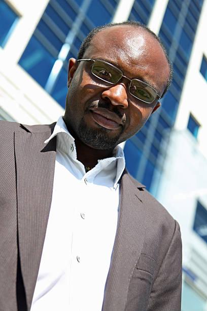 Afroamerikanischer Geschäftsmann auf der Suche nach unten und trägt Brille – Foto