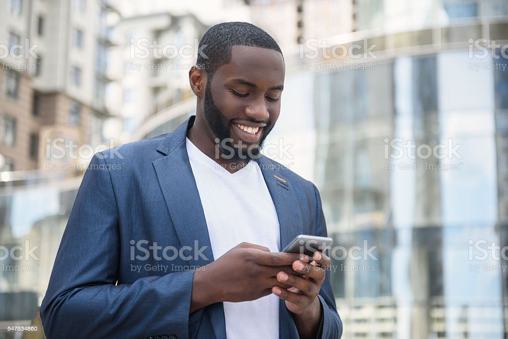 African businessman messaging in big city stock photo