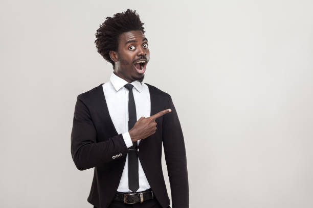 african businessman pointing finger at copy space . studio shot, gray background - excited emoji stock photos and pictures
