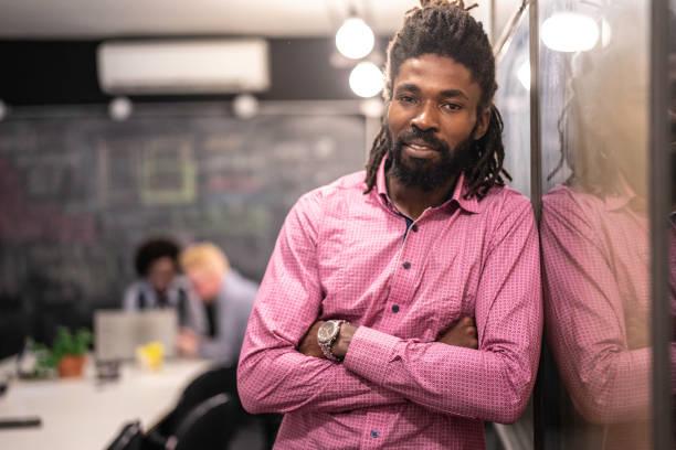 現代のスタートアップ企業におけるアフリカのビジネスマンの肖像 - 背景に人 ストックフォトと画像