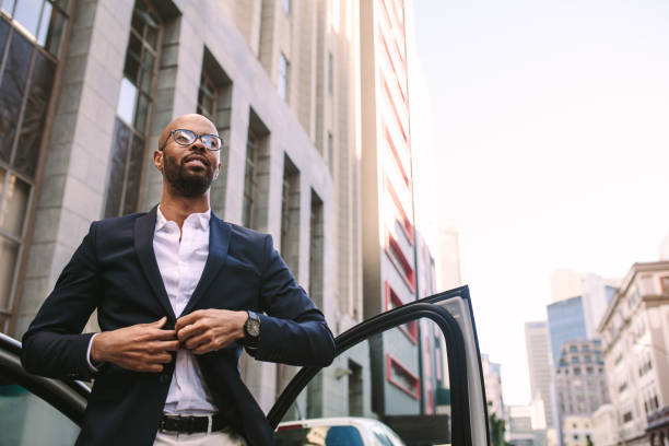 African businessman reached office Portrait of a handsome young businessman getting down from car on road and buttoning his jacket. African man standing by his car in city. driver occupation stock pictures, royalty-free photos & images