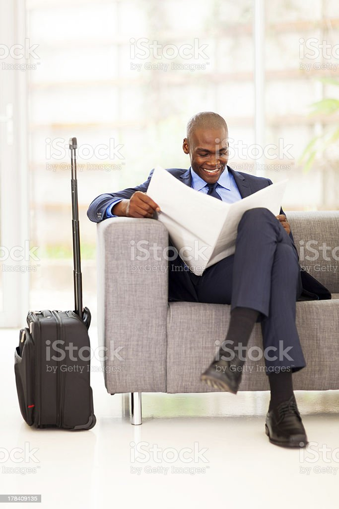 african businessman reading newspaper in airport stock photo