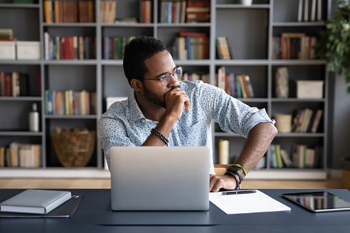 Thoughtful doubtful African businessman in tension sitting at workplace desk near laptop distracted from work makes difficult decision looking at window feels uncertain thinking over problem solution
