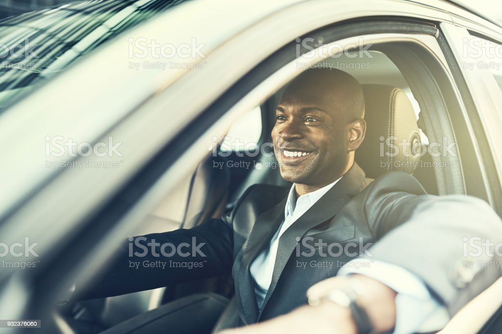 African businessman smiling while driving his car in the city stock photo