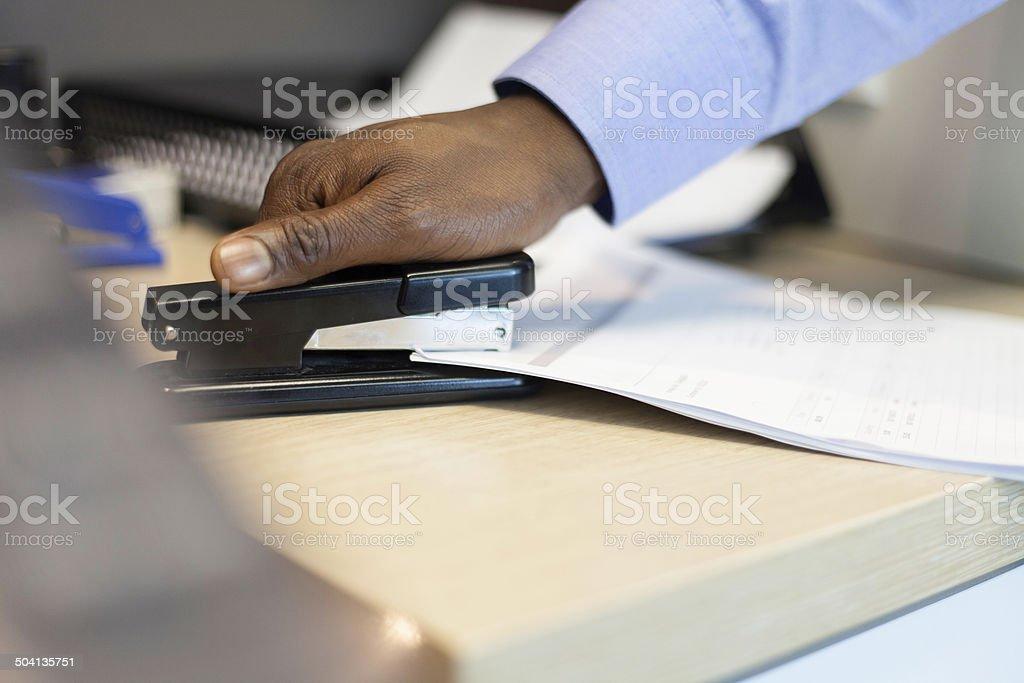 Empresário africano agrafos documentos em conjunto. - fotografia de stock