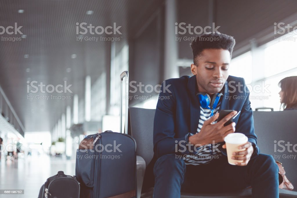 African businessman using cell phone at airport stock photo