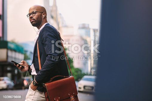 African businessman with bag walking on the street with mobile phone. Handsome businessman listening music from smart phone while walking on city street.