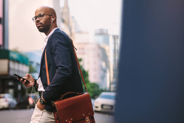 afrikaanse zakenman met zak lopen op straat - forens stockfoto's en -beelden