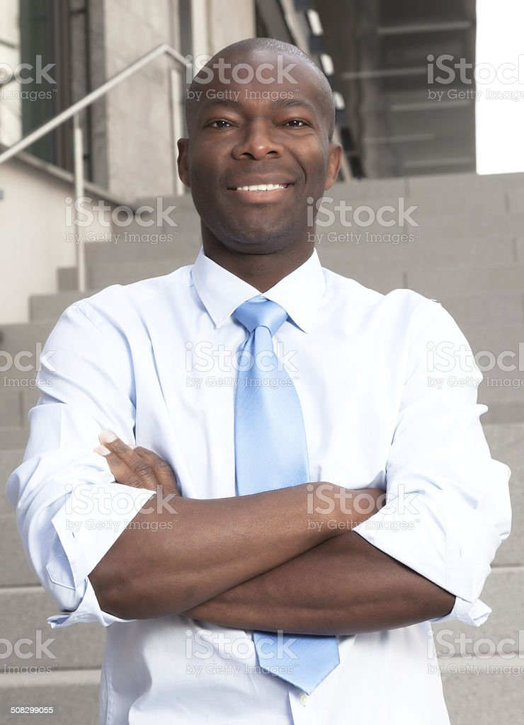 African businessman with crossed arms on stairs stock photo