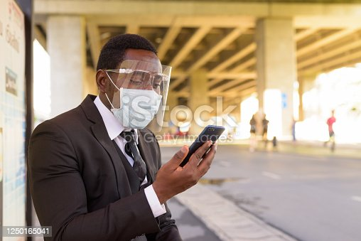 Portrait of African businessman with mask for protection from corona virus outbreak at the bus stop in the city outdoors