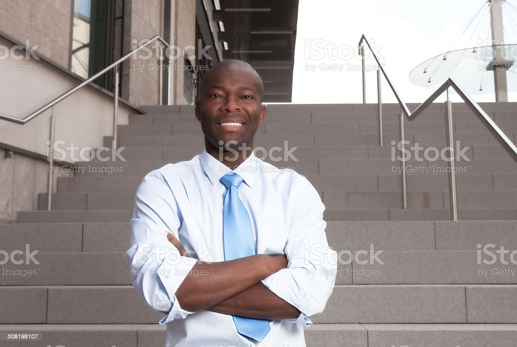 African businessman with stairs in the background stock photo