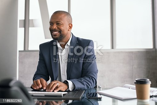 African american businessman working on his laptop at office. Mature business man in formal clothing working at his desk. Smiling black middle aged man sitting in modern office working on computer and checking email.