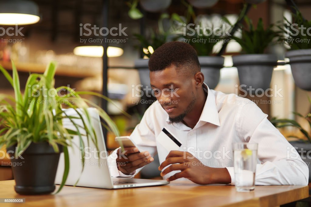 African businessman working with laptop and paying with credit card African businessman working with laptop in cafe, using smart phone, typing, paying with credit plastic card. Student buying in internet shop, sending money from card with gadget. Internet shopping. African Ethnicity Stock Photo