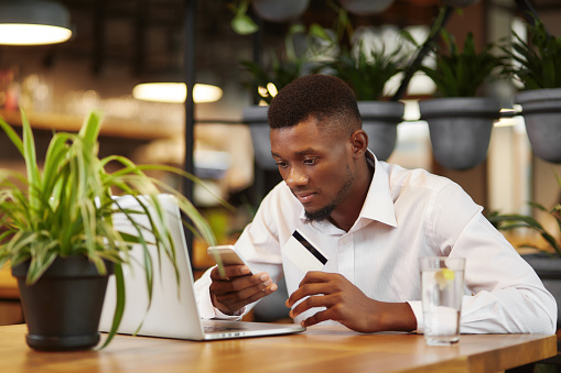 istock African businessman working with laptop and paying with credit card 853935008